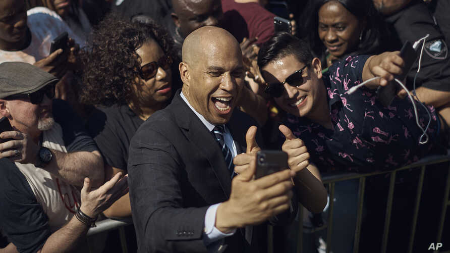 Cory Booker takes a selfie with supporters during a hometown kickoff of his presidential campaign tour at Military Park in downtown Newark, N.J., April 13, 2019.