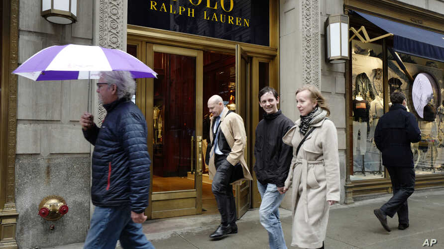 FILE - People pass the Polo Ralph Lauren store on Fifth Avenue in New York, April 4, 2017.
