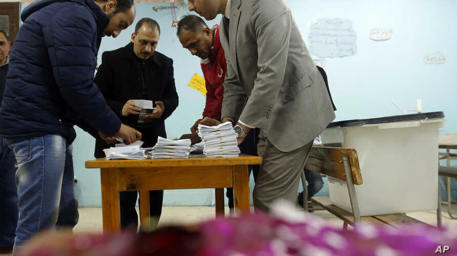 In front of inked tissues, election workers count ballots at the end of three-day vote of the referendum on constitutional amendments at polling station in Cairo, Egypt, Monday, April 22, 2019.