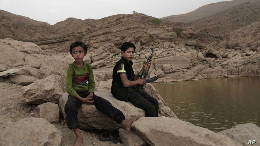"In this July 30, 2018, photo, a 17 year-old boy holds his weapon in High dam in Marib, Yemen. Experts say child soldiers are ""the firewood"" in the inferno of Yemen's civil war, trained to fight, kill and die on the front lines. (AP Photo/Narima..."