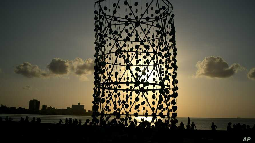 """People walk around an art installation during the inauguration of the exhibition """"Behind the Wall,"""" at the 13th Havana Biennial, in Havana, Cuba, April 14, 2019. American and international artists have flocked to Havana's Biennial, an art show design..."""