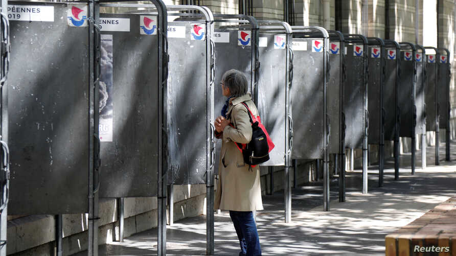 A woman looks at official European election posters outside a polling station in Paris, France, May 13, 2019.