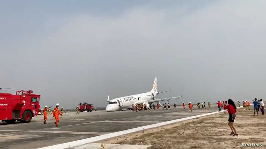 An evacuated passenger records on her phone as firefighters attend to the scene after Myanmar National Airlines flight UB103 landed without a front wheel at Mandalay International Airport in Tada-U, Myanmar, May 12, 2019 in this still image taken fro...