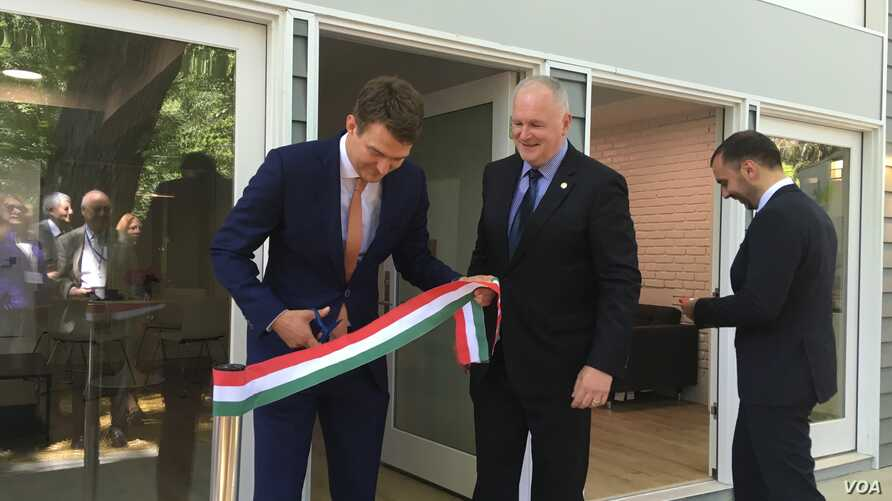 Hungarian State Secretary for Economic Strategy László György, left, cuts a ribbon, styled after the Hungarian flag, as Ambassador László Szabó, center, looks on at the opening ceremony of a business promotion center in Washington, June 12, 2019.