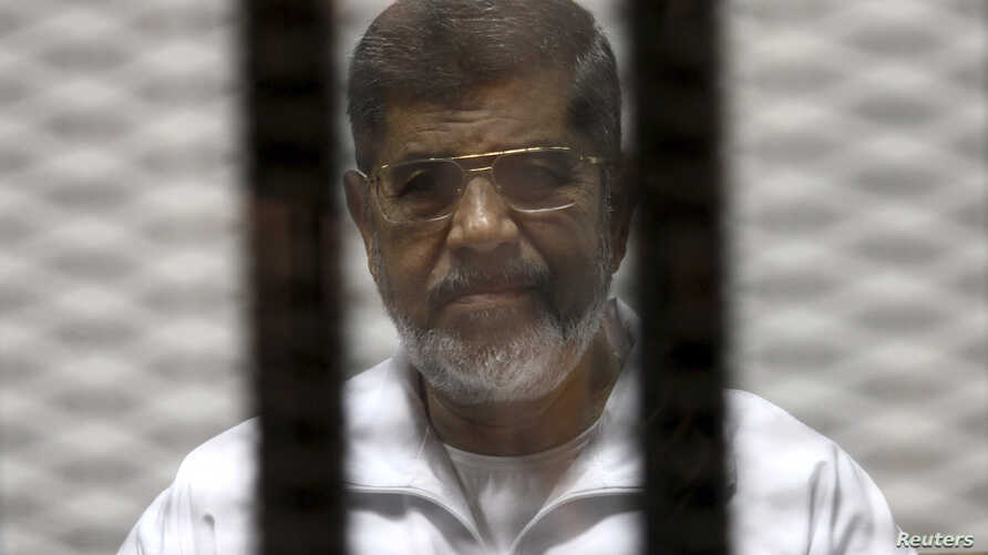 FILE - Ousted Egyptian President Mohamed Morsi is seen behind bars during his trial at a court in Cairo, May 8, 2014.