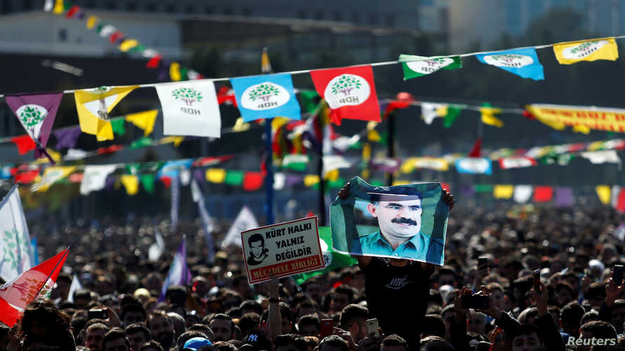 A man holds a picture of jailed Kurdistan Workers Party (PKK) leader Abdullah Ocalan as people gather to celebrate Newroz, which
