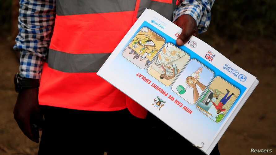An Ugandan health worker shows an informational flyer on Ebola virus and how to prevent its spread to the community of Kirembo village, near the border with the Democratic Republic of Congo, in Kasese district, Uganda, June 15, 2019.