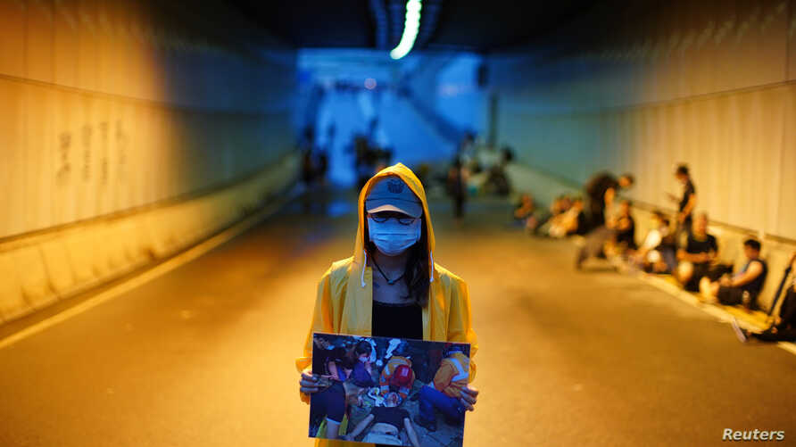 A protester holds a picture of an injured demonstrator, during a demonstration demanding Hong Kong's leaders to step down and withdraw the extradition bill, in Hong Kong, China, June 17, 2019.