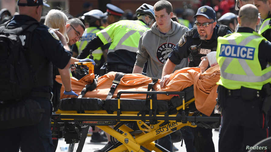 A woman is taken away by ambulance after reports of shots fired in the area where crowds gathered to celebrate the Toronto Raptors victory parade in Toronto, Ontario, Canada, June 17, 2019.