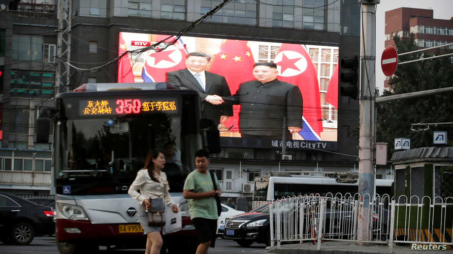 A television screen shows Chinese state media CCTV's footage of North Korean leader Kim Jong Un's meeting with Chinese President Xi Jinping in Pyongyang, at a street in Beijing, China, June 20, 2019