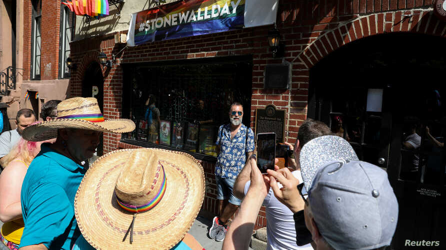 People gather outside The Stonewall Inn, on the 50th anniversary of the Stonewall Riot, in the Greenwich village area of New York, U.S., June 28, 2019.