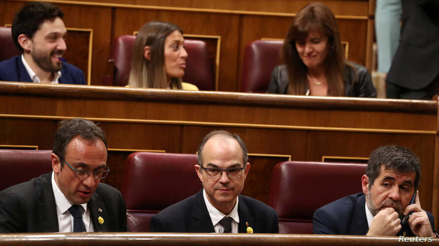 FILE - Jailed Catalan politicians Jordi Sanchez, Josep Rull and Jordi Turull attend the first session of parliament following a general election in Madrid, Spain, May 21, 2019.