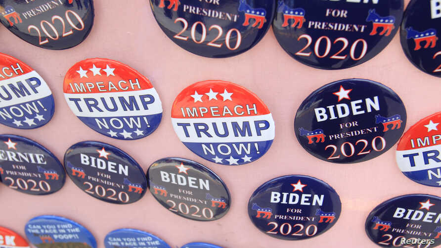"FILE - Biden for President campaign buttons are for sale beside ""Impeach Trump Now!"" buttons as U.S. Democratic presidential candidate and former Vice President Joe Biden meets union workers at the Teamsters Local 249 hall  in Pittsburgh, Pa., April 29, 2019."