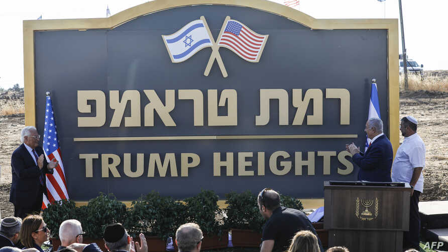 """Israeli Prime Minister Benjamin Netanyahu (2nd-R) and U.S. Ambassador to Israel David Friedman (L) applaud after unveiling the place-name sign for the new settlement of """"Trump Heights"""" during a ceremony in the Israeli-annexed Golan Heights, June 16, 2019."""