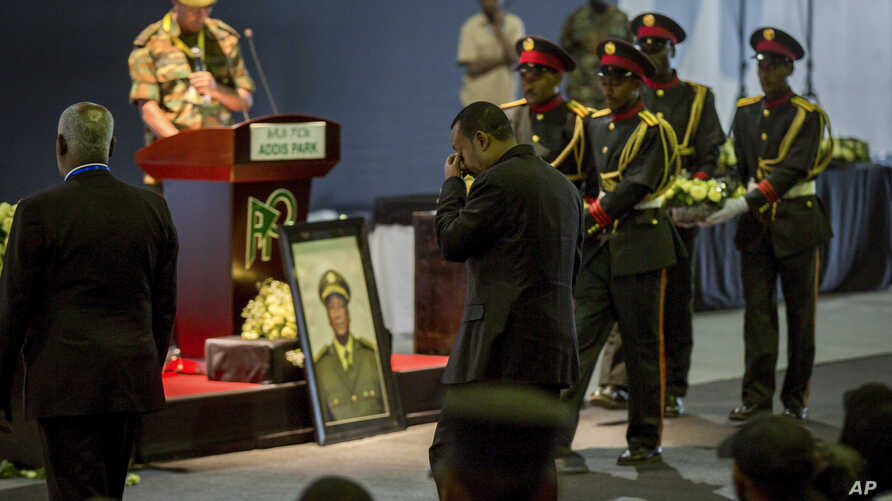 Ethiopia's Prime Minister Abiy Ahmed, center, attends a state ceremony for assassinated army chief Gen. Seare Mekonnen, at the Millennium Hall in the capital Addis Ababa, Ethiopia, June 25, 2019.