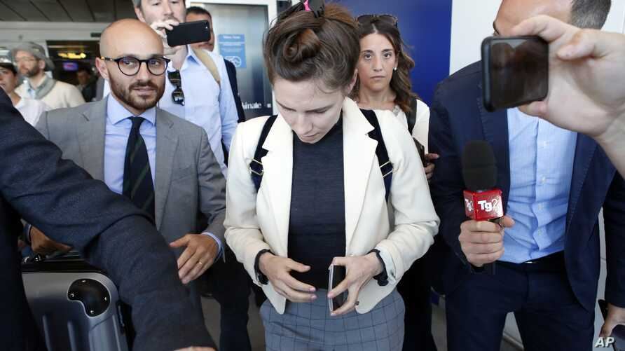 Amanda Knox, center, is approached by journalists upon her arrival in Linate airport, Milan, Italy, June 13, 2019.