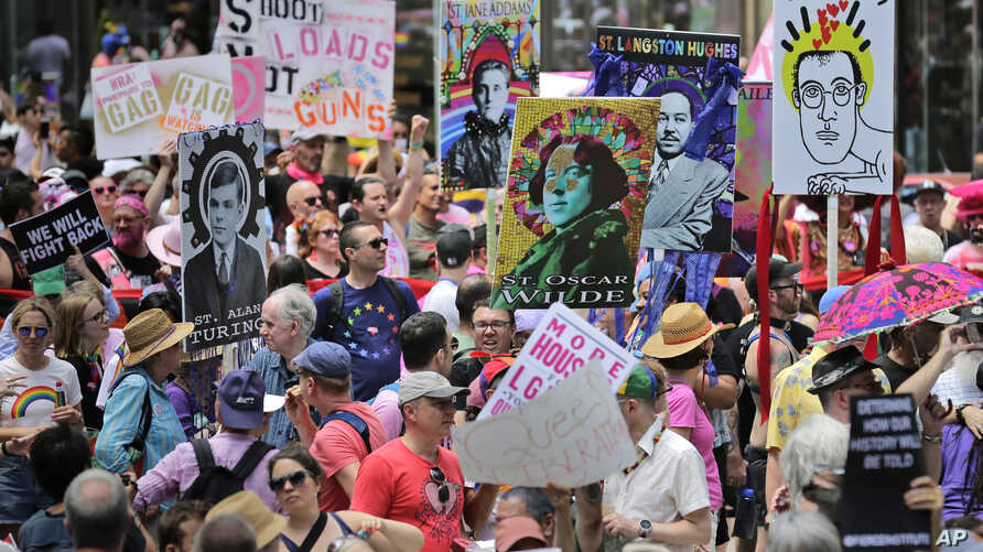 Marchers carry signs with historical LGBTQ figures during the Queer Liberation March in New York, Sunday, June 30, 2019.