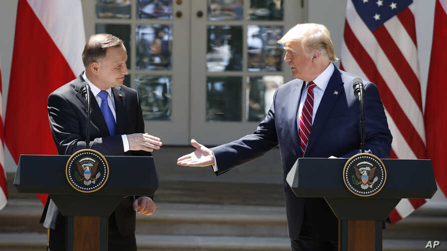 President Donald Trump and Polish President Andrzej Duda reach to shake hands at a news conference in the Rose Garden of the White House, in Washington, June 12, 2019.