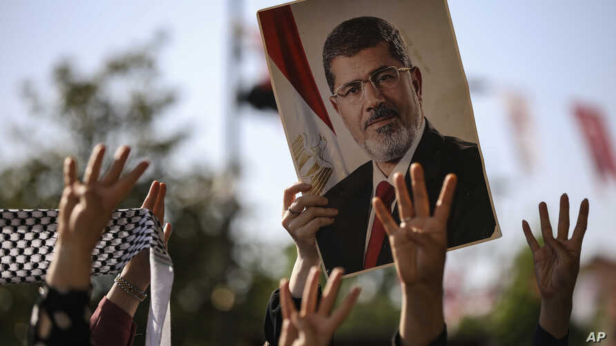 A person holds a picture of the late former Egyptian President Mohamed Morsi during a symbolic funeral ceremony, June 18, 2019 at Fatih mosque in Istanbul, Turkey.