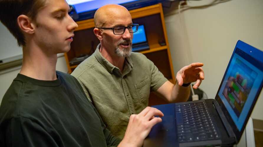 Luke Trinity and Scott Merrill are part of a team of University of Vermont researchers using video games and computational models to understand human behavior. (Sally McCay/University of Vermont)