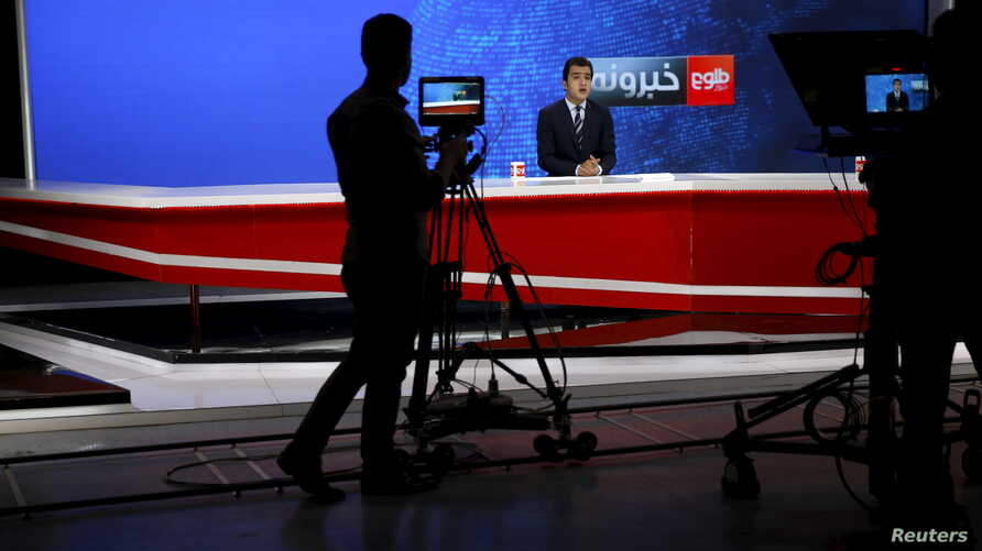 FILE - A news anchor is seen on camera during a broadcast at Tolo News studio, in Kabul, Afghanistan, Oct. 18, 2015.