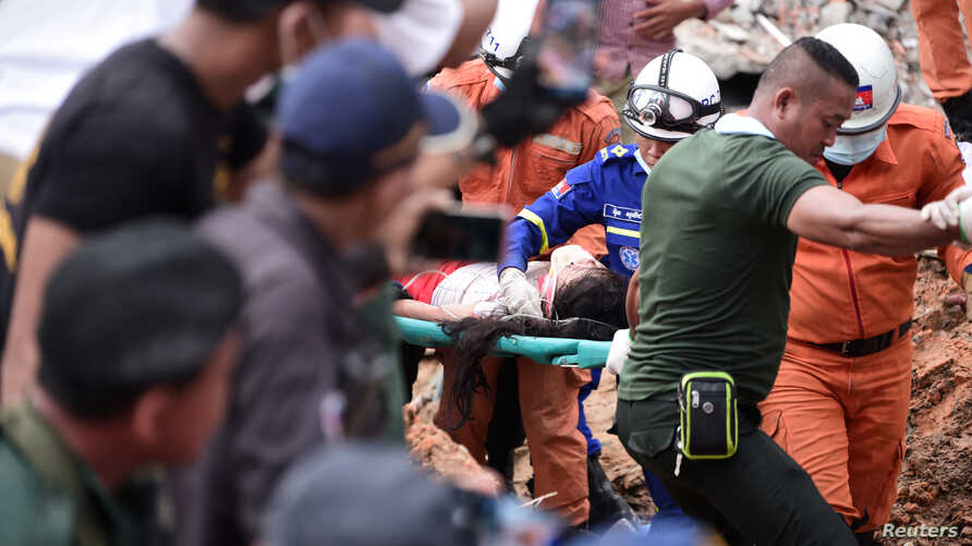 A rescue team carries a wounded worker at a collapsed building in Sihanoukville, Cambodia, June 22, 2019.