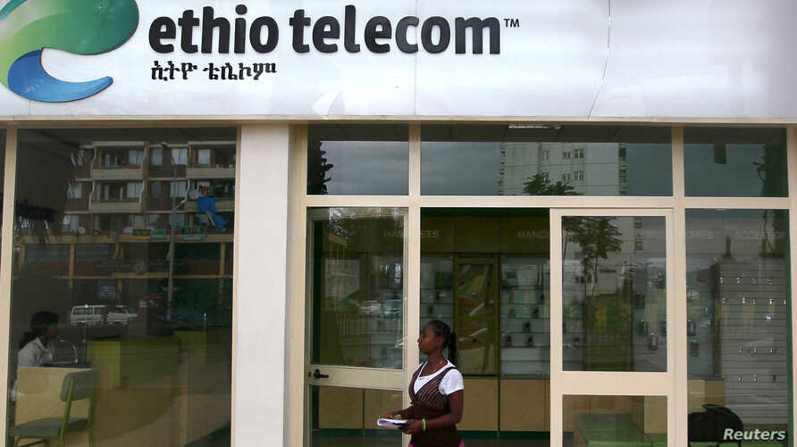FILE - A woman walks past an office of Ethio Telecom, a state monopoly, in Ethiopia's capital, Addis Ababa, Nov. 9, 2015.