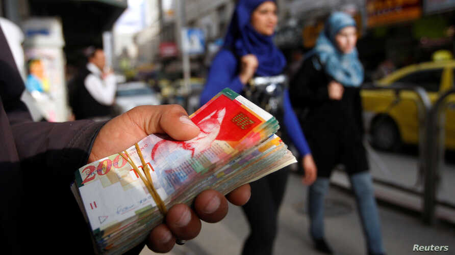 Palestinian women walk past a money changer in the West Bank city of Ramallah, Feb. 16, 2010.