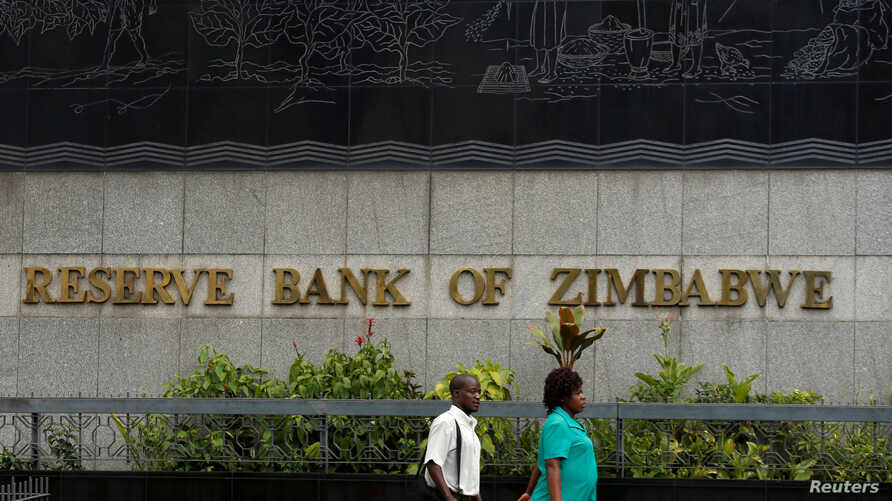 FILE - People walk past the Reserve Bank of Zimbabwe building in Harare, Zimbabwe, February 25, 2019.