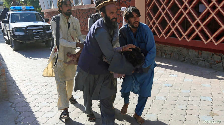 Afghan men carry a wounded person to the hospital after a suicide attack in Jalalabad, Afghanistan, June 13, 2019.