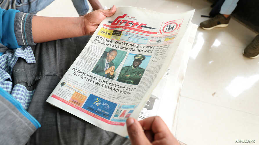 An Ethiopian man reads a newspaper with the pictures of Amhara state President Ambachew Mekonnen, killed in Bahir Dar, and of Army Chief of Staff Seare Mekonnen, who was shot by his bodyguard, on a street in Addis Ababa, June 24, 2019.