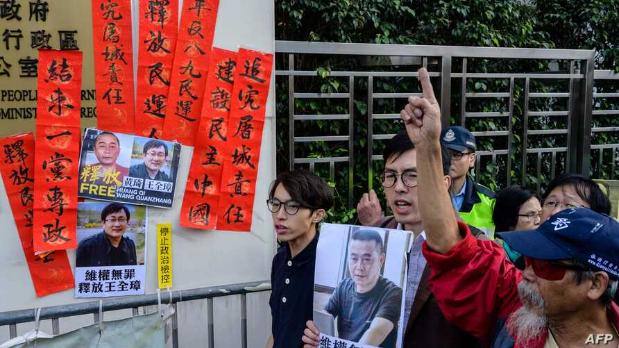 "FILE - Hong Kong pro-democracy activists hold a placard, at right, that reads ""rights activism is not wrong, free Huang Qi"" during a protest outside the Chinese Liaison Office in Hong Kong, Jan. 29, 2019."