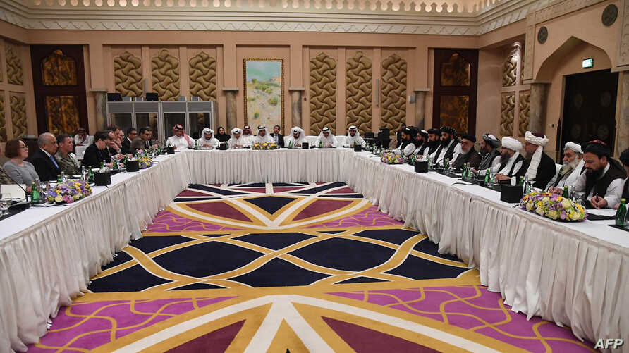 FILE - A handout photo released by the official Qatar's Ministry of Foreign Affairs on Feb. 26, 2019, shows Qatari officials, center, taking part in meeting between the U.S. delegation, left, and the Taliban delegation in Doha.