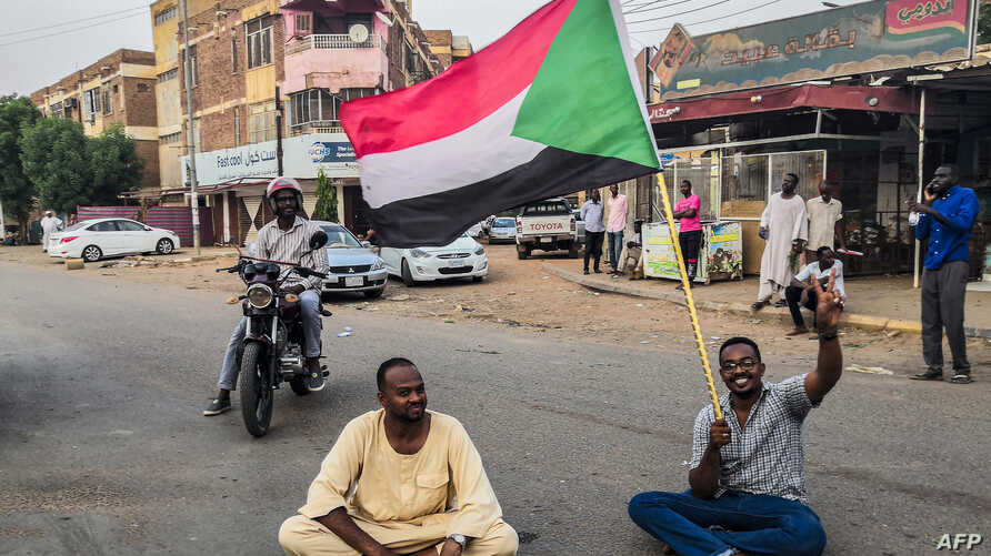 A Sudanese man sits with another in a street while waving a national flag during a mass demonstration against the country's ruling generals in the capital Khartoum, June 30, 2019.