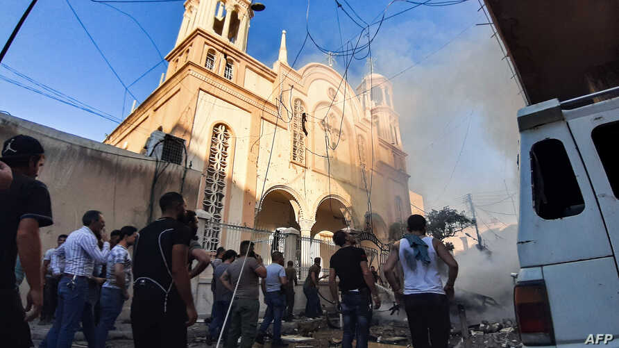 People gather at the scene of a car bomb explosion outside the Syriac Orthodox Church of the Virgin Mary in the predominantly Christian neighborhood of al-Wasti in the Kurdish-majority city of Qamishli in northeast Syria, July 11, 2019.