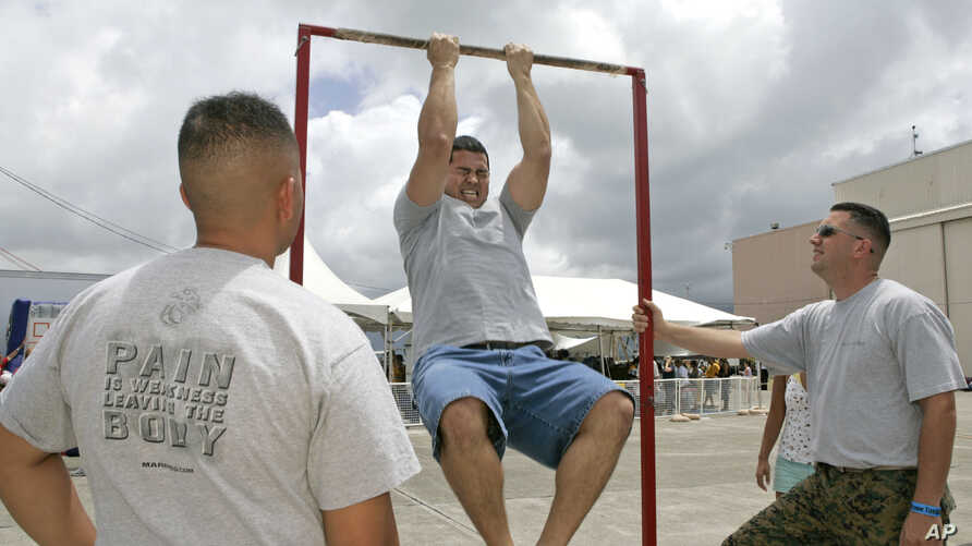 FILE - Matt Elam, center, competes in a US Marine pull-up contest while Marine recruiters watch.