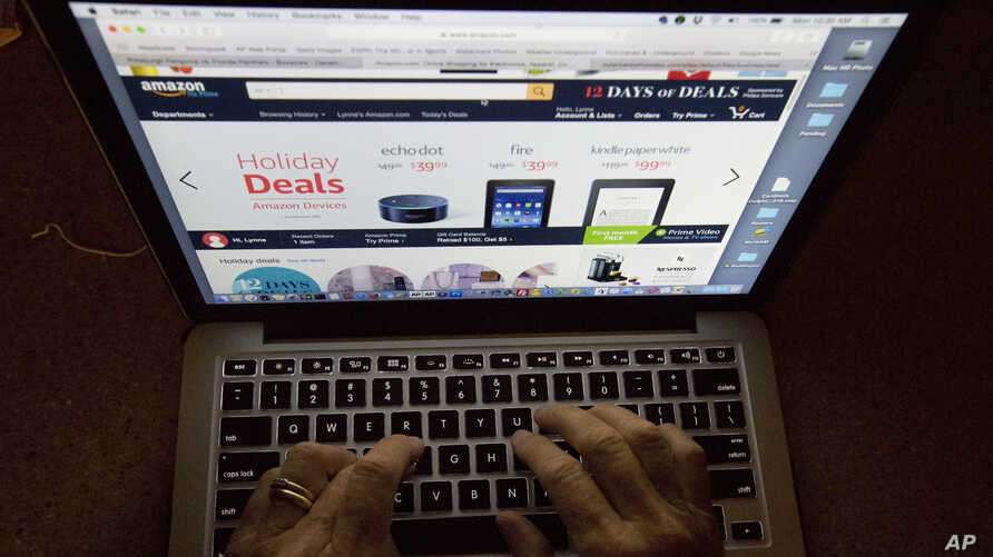 FILE - An online shopper searches Amazon's website showing holiday deals.