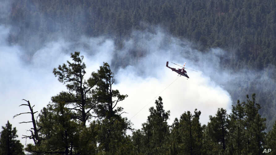 FILE - The U.S. Forest Service shows a helicopter fighting a wildfire in Coconino National Forest in Arizona, April 30, 2018. Visitors at the park have been asked to evacuate after a fire in the state grew to more than 400 hectares on July 22, 2019.