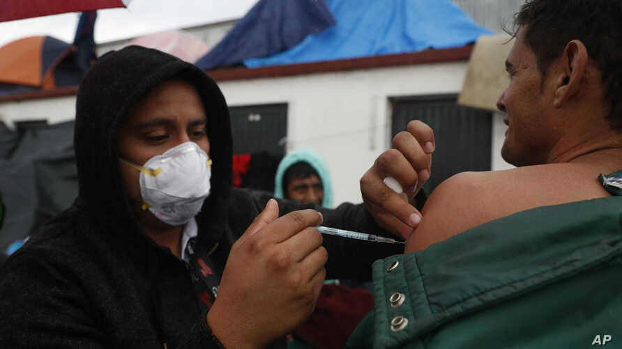 FILE - Mexican Health Ministry representatives give migrants free shots for the flu, hepatitis B, tetanus, and preventible children's diseases at the Barretal shelter for migrants in Tijuana, Mexico, Dec. 6, 2018.