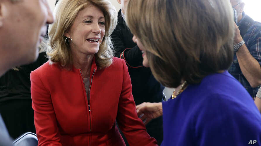 FILE - Former state senator Wendy Davis, center, visits with Speaker of the House Nancy Pelosi, D-Calif., (R), following a stop for a news conference, March 5, 2019, in Austin, Texas.