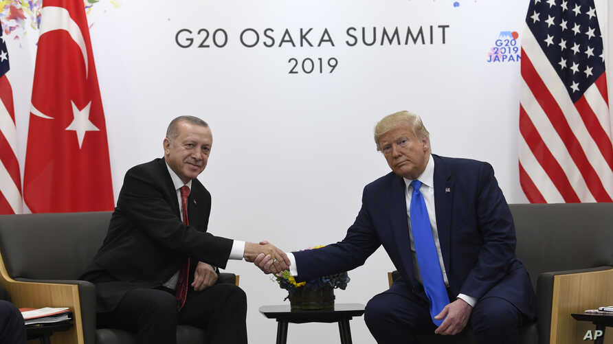 FILE - President Donald Trump, right, shakes hands with Turkish President Recep Tayyip Erdogan during a meeting on the sidelines of the G-20 summit in Osaka, Japan, June 29, 2019.