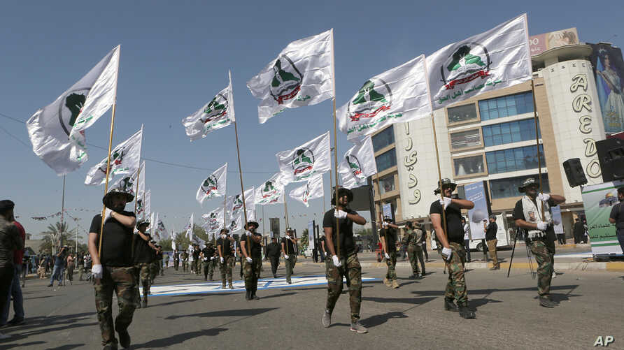 FILE - Iraqi Popular Mobilization Forces march as they hold Popular Mobilization flags in Baghdad, Iraq, May 31, 2019. Iraq's government is placing Iran-backed militias under the full command of the Iraqi armed forces.