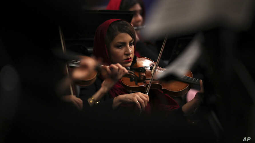 An Iranian musician plays the violin while performing pieces by 19th-century Russian composers in Tehran Symphony Orchestra at Unity Hall, in Tehran, Iran, July 3, 2019.