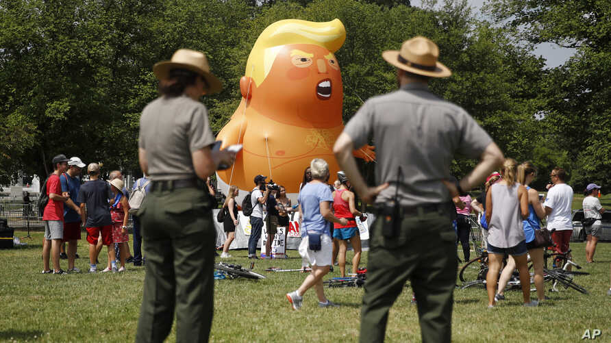 National Park Service rangers view a Baby Trump balloon before Independence Day celebrations on the National Mall in Washington, July 4, 2019.