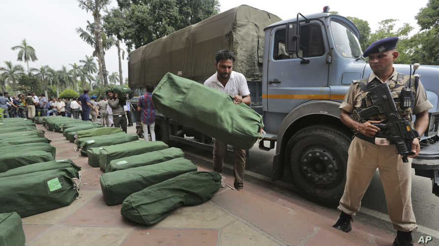 An Indian security man stands guard as a worker places a bag carrying federal budget copies for the year 2019- 20, that will be distributed to lawmakers at the parliament house in New Delhi, India, Friday, July 5, 2019.