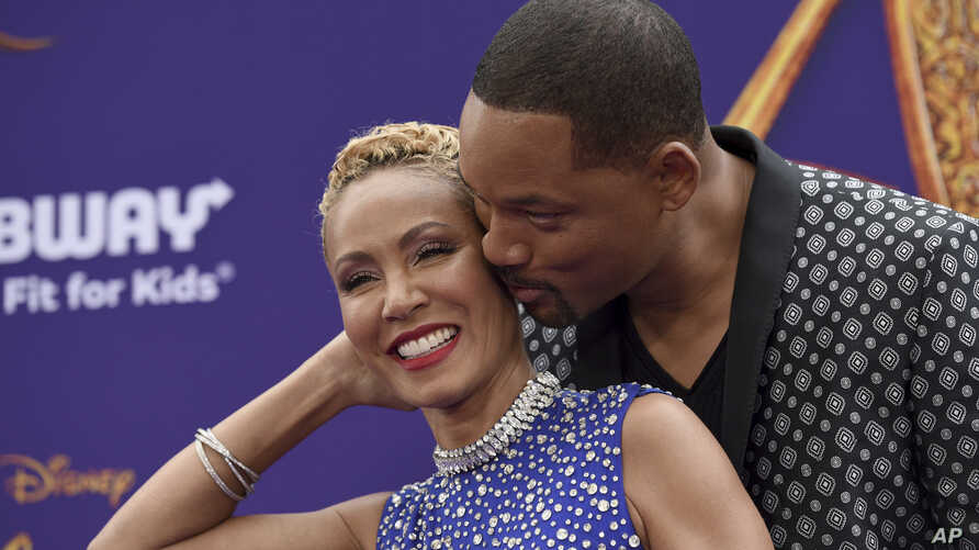 "FILE - Will Smith, right, kisses Jada Pinkett Smith as they arrive at the premiere of ""Aladdin"" at the El Capitan Theatre in Los Angeles, May 21, 2019."