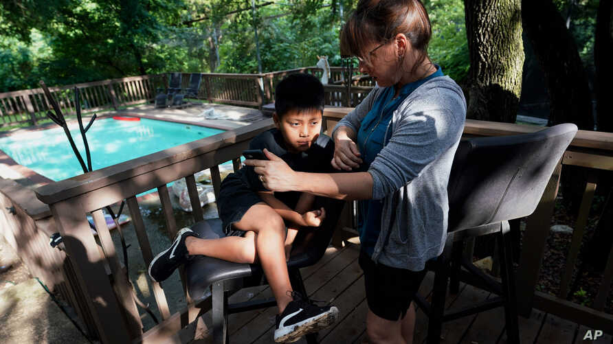 FILE - Holly Sewell helps Byron Xol, 9, an immigrant from Guatemala, talk to his family by phone, June 24, 2019, in Buda, Texas.