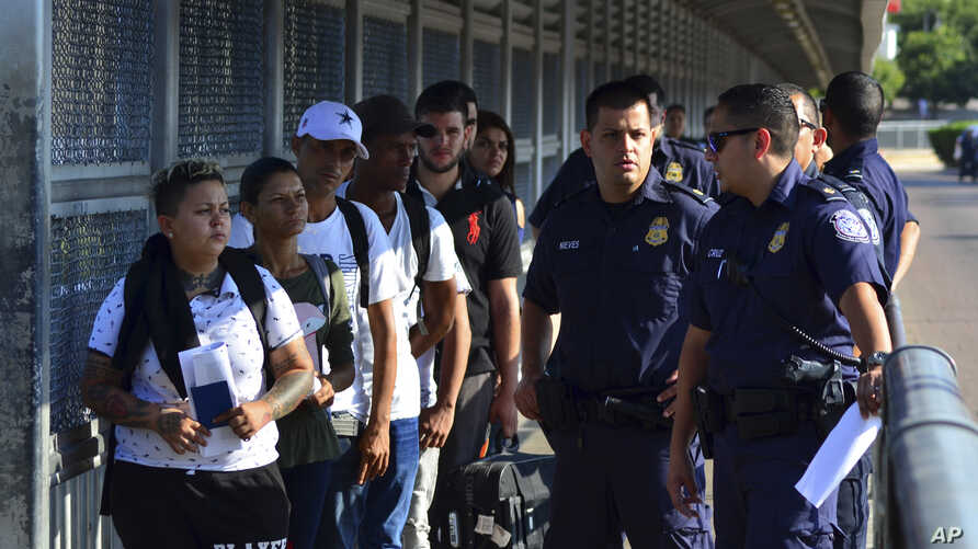 US Customs and Border Patrol officials wait to hand asylum-seekers over to Mexican officials as they are returned  under the so-called Remain in Mexico program, on the international bridge between Laredo, Texas, and Nuevo Laredo, Mexico, July 10, 2019.