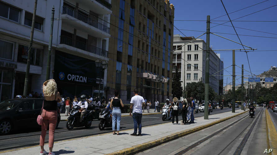 People stand outside the building they work in after a strong earthquake hit near the Greek capital of Athens, July 19, 2019.