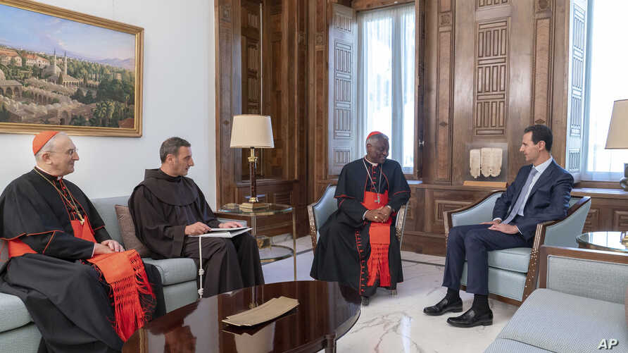 In this photo released on the official Facebook page of the Syrian Presidency, Syrian President Bashar al-Assad, right, meets Cardinal Peter Turkson, second right, in Damascus, Syria, July 22, 2019.